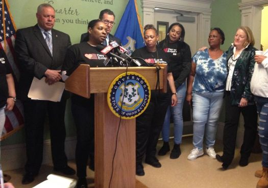 Department of Correction Commissioner Scott Semple, left, and Gov. Dannel P. Malloy stand behind Taiheba Bain, a formerly incarcerated woman, as she describes the need for a bill addressing women's experience in prison on Tuesday at a halfway house in Hartford. To their left stand three other formerly incarcerated women, and Cathy Malloy, the governor's wife. Josie Albertson-Grove/Republican-American