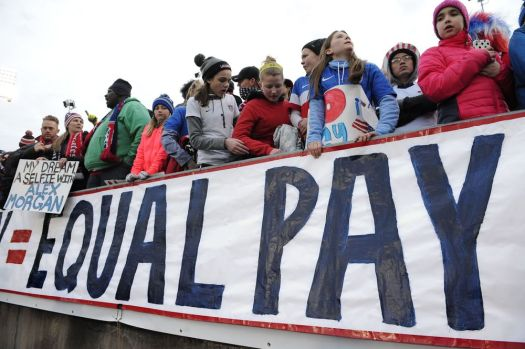 In this April 6, 2016, file photo, fans stand behind a large sign for equal pay for the women's soccer team during an international friendly soccer match between the United States and Colombia at Pratt & Whitney Stadium at Rentschler Field in East Hartford, Conn. The World Economic Forum's annual Global Gender Gap Report released on Oct. 25, 2016, found that the global gender pay gap will not be closed for another 170 years if current trends continue. (AP Photo/Jessica Hill, File)