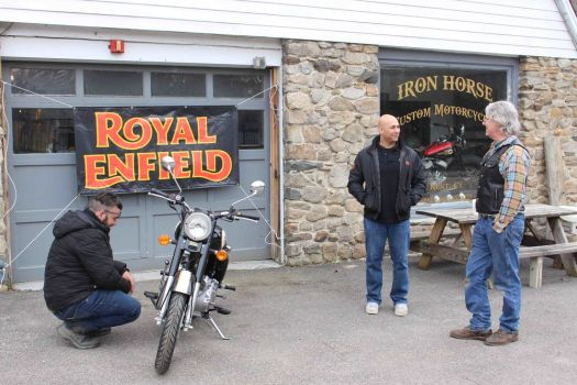 Royal Enfield regional manager Omar Buker, center, talks with Iron Horse Custom's co-owner Rock Dolson, right, shortly after the new dealership in Kent received its first shipment of motorcycles on Wednesday morning. Antonio