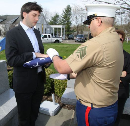 Jonathan Phair, left, of New Canaan, grandson of American Legion Post 44 veteran of the month Richard J. Phair, presents a flag in his late grandfather's honor to Post 44 representative Karl Crump during the veteran of the month service at the All Wars Memorial in Bantam on Saturday. John McKenna / Republican-American
