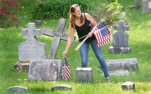 Georgi Andrews Goodell of Winsted replaces old American flags with new ones Friday at New St. Joseph's Cemetery on Oak Street in Winsted. Andrews and her children help replace the flags at that cemetery every year before Memorial Day. Steven Valenti Republican-American