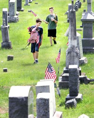Caleb Goodell, left, and Mason Goodell, both 14, of Winsted, help their family replace old American flags with new ones Friday at New St. Joseph's Cemetery on Oak Street in Winsted. The family replaces the flags at that cemetery every year before Memorial Day. Steven Valenti Republican-American