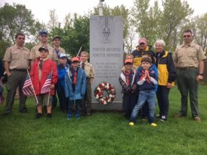 Scouts and adults from Pack 3 of Torrington and the Torrington Civitan Club pose after placing a wreath in front of a monument that honors veterans at the New St. Francis Cemetery in Torrington. These Scouts and Civitan members helped place American flags on the graves of veterans in Hillside and New St. Francis cemeteries on May 12. Contributed