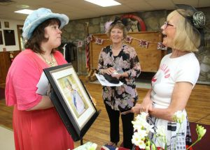 GOSHEN, CT - 19 May 2018 - 051918JM02 - Janice Connor, right, of Goshen, host of a royal wedding party at Camp Cochipianee in Goshen on Saturday, chats with Kathryn Rosenfield, left, of Goshen and Rosenfield's mother-in-law, Robin Rosenfield of Goshen, during the event. John McKenna Photo