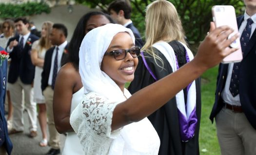 WASHINGTON CT. 28 May 2018-052818SV02- Yamna Abdi Jama of Somaliland, West Africa , had special permission to use her phone during graduation so she could stream the graduation live for her mother to watch in West Africa during the graduation ceremony at The Gunnery School in Washington Monday. Steven Valenti Republican-American