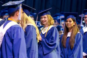 Lewis Mills graduates Katherine Burns, left, and Jordan Butler wait in line for their diplomas Thursday at the Warner Theatre in Torrington. Jim Shannon Republican American