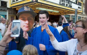 Lewis Mills graduate Jackson Lord holds a big likeness of himself as he poses for a photo following graduation Thursday at the Warner Theatre in Torrington. The 'baseball head' was given to him by his mother, Lori Jones, right. Jim Shannon Republican American