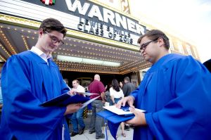 Lewis Mills graduates Eli Jones, left, and Austin Hendel check out their diplomas following the ceremony Thursday at the Warner Theatre in Torrington. Jim Shannon Republican American