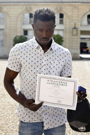Mamoudou Gassama, 22, from Mali, displayed a certificate of courage and dedication signed by Paris Police Prefect Michel Delpuech as he leaves the presidential Elysee Palace after his meeting with French President Emmanuel Macron, in Paris, Monday, May, 28, 2018. Mamoudou Gassama living illegally in France is being honored by Macron for scaling an apartment building over the weekend to save a 4-year-old child dangling from a fifth-floor balcony. (AP Photo/Thibault Camus, Pool)