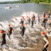 Swimmers sprint into the water for their half mile swim during the the 32nd annual Pat Griskus Sprint Triathalon at Quassy Amusement Park in Middlebury, CT on Wednesday evening. Bill Shettle Republican-American
