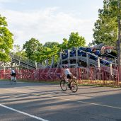 Bikers on the second leg of the Triathlon ride by riders on the roller coaster during the the 32nd annual Pat Griskus Sprint Triathalon at Quassy Amusement Park in Middlebury, CT on Wednesday evening. Bill Shettle Republican-American