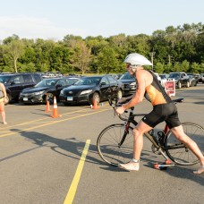 Triathlete Arthur Boyko of NY gets ready to get off his bike by transitioning from biking to running during the the 32nd annual Pat Griskus Sprint Triathalon at Quassy Amusement Park in Middlebury, CT on Wednesday evening. Bill Shettle Republican-American