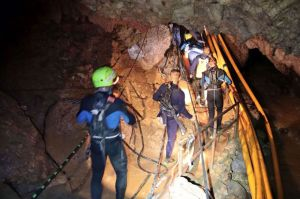 In this undated photo released by Royal Thai Navy on Saturday, July 7, 2018, Thai rescue team members walk inside a cave where 12 boys and their soccer coach have been trapped since June 23, in Mae Sai, Chiang Rai province, northern Thailand. The local governor in charge of the mission to rescue them said Saturday that cooperating weather and falling water levels over the last few days had created appropriate conditions for evacuation, but that they won't last if it rains again. (Royal Thai Navy via AP)