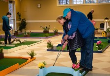 WOODBURY, CT. 15 February 2019-021519 - Don Adams, still thinking it's Valentines Day, shows his wife Terry how to hit the ball as they play the indoor mini-golf course at the Senior Center in Woodbury on Friday. Bill Shettle Republican-American