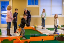 WOODBURY, CT. 15 February 2019-021519 - From left, Grandma Betsy Daniels, Elliott Shugrue, 9, Gavin Clampett, 7, Brynn Clampett, 10, and Autumn Shugrue, 6, all look on watching Great grandmother Elizabeth Barry hit the ball, as they play the indoor mini-golf course at the Senior Center in Woodbury on Friday. Bill Shettle Republican-American