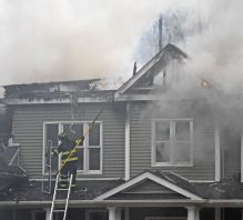 A Northville firefighters stands on a roof with flames and smoke coming through the second story Sunday afternoon during a fire that badly damaged the home of Marika and Kim Coolbeth at 17 Tamshell Drive in the Kent Hollow section of town. Lynn Mellis Worthington Republican-American