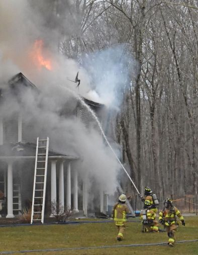 Firefighters aim hoses at the flames coming through the roof Sunday afternoon during a fire that badly damaged the home of Marika and Kim Coolbeth at 17 Tamshell Drive in the Kent Hollow section of town. Lynn Mellis Worthington Republican-American