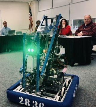 Region 14 Board of Education members, from left, George Bauer, Dave Lampart, Pamela Zmek and Mike Devine watch Team Beta's robot 'Bruiser' perform during a meeting Monday.Steve BighamRepublican-American