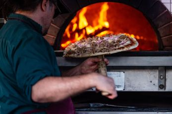 Another pizza goes in the wood-fired brick oven during the Greater Waterbury Campership Fund's Big Green Truck party at Camp Mataucha in Watertown on Thursday. Bill Shettle Republican-American