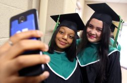 From left, Mariel Belen, 18, and Diana Aleman, 18, both of Waterbury take a photo during the Wilby High graduation at the Palace Theater in Waterbury Friday. Steven Valenti Republican-American