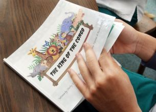 Students look over one of the books the CNA students are putting together at Wilby High School in Waterbury Monday. The CNA students are finishing up an illustrated book they will distribute to youngsters in area hospitals. Steven Valenti Republican-American