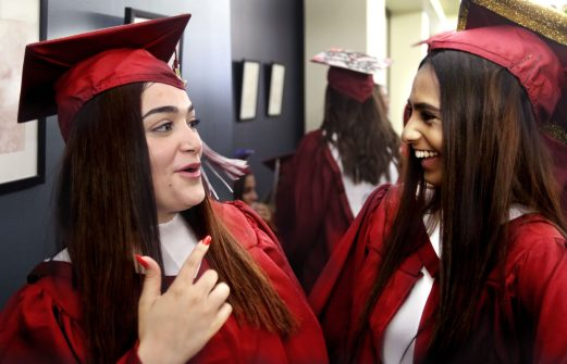 From left, Aaliyah Rivera, 17, and Katie Azeez, 17 both of Torrington celebrate during graduation at the Warner Theater in Torrington Sunday. Steven Valenti Republican-American