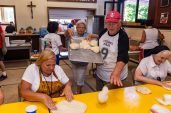 WATERBURY, CT. 12 July 2019-071219 - Jack Varanelli of Waterbury, center, tosses dough to the woman to knead out as Elda Michele grabs some dough from his tray, during the second night of the 81st annual Italian Feast of Our Lady of Mount Carmel at Our Lady at Mount Carmel in Waterbury on Friday. Bill Shettle Republican-American