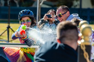 Carmella Ibarra with the team from Waterbury Health, sprays a water gun at the Thomaston Savings Bank team after receiving the benefit of the Bed Wetter challenge during the third annual United Way of Greater Waterbury's Bed Races held in downtown Waterbury on Saturday. The event is a fundraiser for the United Way. Jim Shannon Republican-American
