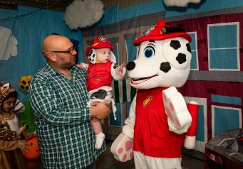 SOUTHBURY, CT. 26 October 2019-102619BS386 - Little Marshall John Parlante 1 1/2 of Manchester, center, reaches out and touches the nose of big Marshall of PAW Patrol, as he is held by his father Ron Parlante, during the ninth Annual Trick-or-Treat Spooktacular at the Southbury Center Firehouse on Saturday. The firehouse was transformed into a maze of different themed-rooms where kids could collect treats. Bill Shettle Republican-American