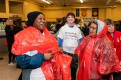 WATERBURY, CT. 27 October 2019-102719BS687 - Alison Bullen, left, and Belinda Dupre, right, two walkers from the team of Naugatuck Valley Community College get ready by put their complimentary ponchos on at Sacred Heart School , as Collin Murphy of Oxford, center, looks on, during the eleventh annual walk and race fundraiser for the St. Vincent DePaul Mission of Waterbury on Sunday. The Walk took the participants through the St. Vincent DePaul Mission's Thrift Store, Soup Kitchen, and Shelter, the same facilities where the poor receive clothing, food, and a place to sleep, with the guidance of Mission staff. Bill Shettle Republican-American