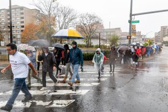 WATERBURY, CT. 27 October 2019-102719BS675 - Walkers walk across the intersection of South Main Street and Union Street in downtown Waterbury in the pouring rain, during the eleventh annual walk and race fundraiser for the St. Vincent DePaul Mission of Waterbury on Sunday. The Walk took the participants through the St. Vincent DePaul Mission's Thrift Store, Soup Kitchen, and Shelter, the same facilities where the poor receive clothing, food, and a place to sleep, with the guidance of Mission staff. Bill Shettle Republican-American