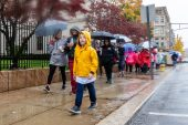 WATERBURY, CT. 27 October 2019-102719BS690 - Max Humphrey, 8, of Middlebury walks in his yellow slicker down Grand Street in the pouring rain, during the eleventh annual walk and race fundraiser for the St. Vincent DePaul Mission of Waterbury on Sunday. The Walk took the participants through the St. Vincent DePaul Mission's Thrift Store, Soup Kitchen, and Shelter, the same facilities where the poor receive clothing, food, and a place to sleep, with the guidance of Mission staff. Bill Shettle Republican-American