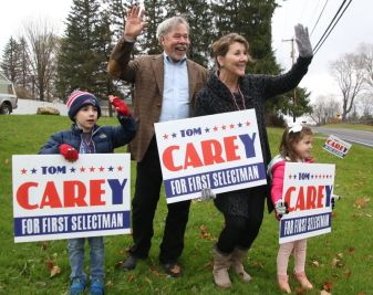 Goshen first selectman candidate Thomas Carey, his wife, Deb, and their grandchildren, Beau Werner, 6, and Lilly Werner, 3, both of Winsted, wave to motorists along Route 4 in Goshen on Tuesday. John McKenna Republican-American