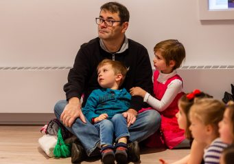 """WOODBURY, CT. 24 November 2019-112419BS214 - Jerry Guz of Bethlehem watches the performance from the floor with his kids Leon, 3, in his lap, and Lily 5, during a performance of the popular Christmas Tale """" The Nutcracker """" for children and families at the Woodbury Public Library gallery on Sunday. Bill Shettle Republican-American"""