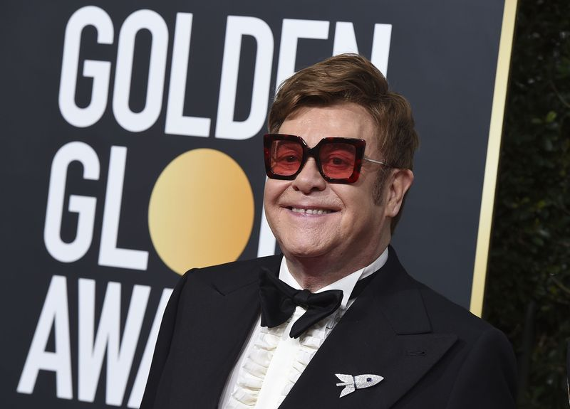FILE - In this Jan. 5, 2020 file photo, Elton John arrives at the 77th annual Golden Globe Awards at the Beverly Hilton Hotel, in Beverly Hills, Calif. An emotional John had to cut short a performance in New Zealand on Sunday, Feb. 16 after he lost his voice due to walking pneumonia and had to be assisted off stage. John reached out to his fans on Instagram on Sunday, apologizing for ending his show at Auckland