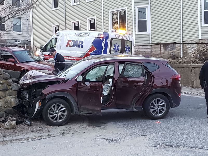 Emergency responders work at the scene of a two-car accident on Brewster Street in Waterbury