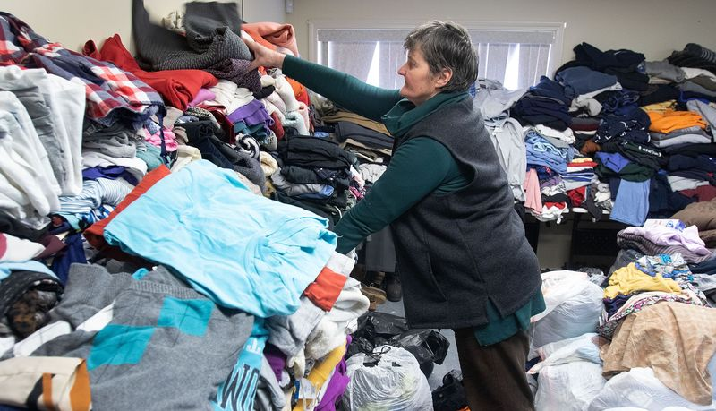 WATERBURY CT - -Zina Petuska, of Waterbury, stacks donated cloths for the homeless at the Center for Human Development in Waterbury on Tuesday. The donation effort was made after fire destroyed the homeless hospitality center. Steven Valenti Republican-American