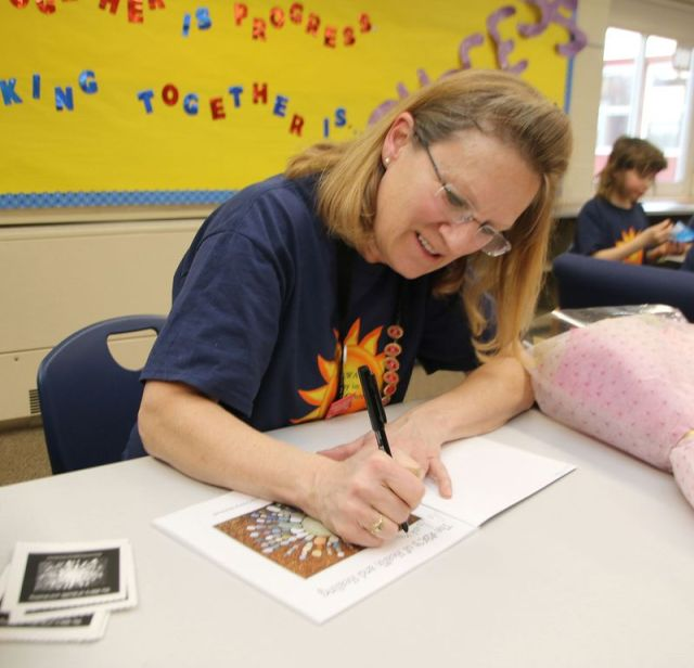 Goshen Center School teacher Cheryl Martinelli signs a copy of her new book during a book signing at the school. John McKenna Republican-American