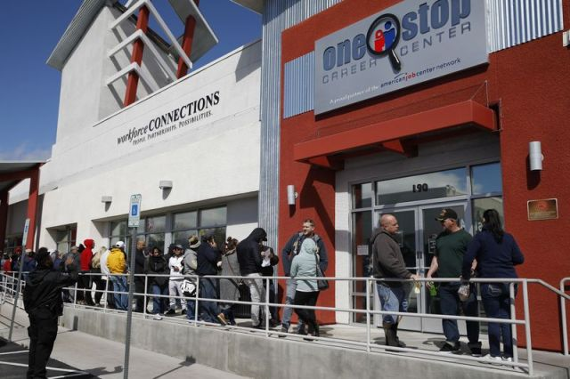 People wait in line for help with unemployment benefits at the One-Stop Career Center, Tuesday, March 17, 2020, in Las Vegas. Nevada Department of Employment, Training and Rehabilitation and its partner organizations, like the One-Stop Career Center, have seen an increase in traffic due to the coronavirus. (AP Photo/John Locher)