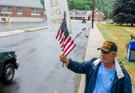 Lou Alba of Woodbury waves an American flag and Blue Lives Matter sign during a rally to support local and national law enforcement Saturday at Seth Thomas Park in Thomaston. Jim Shannon Republican-American