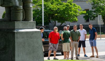 A group of local residents stand in anger and disbelief after someone removed the head of the Christopher Columbus statue in front of Waterbury City Hall in the early hours of Saturday. Jim Shannon Republican-American