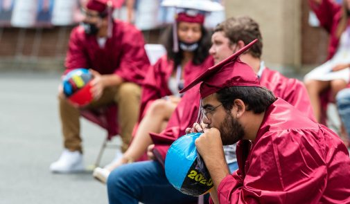 Alexis Garcia kills time before graduation ceremonies by blowing up a complimentary beach ball Friday at Naugatuck High School. The school held five separate ceremonies with about 40 graduates at each due to limitations on gatherings. Jim Shannon Republican-American