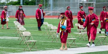 Naugatuck High School graduates make their way to their seats during graduation ceremonies Friday at Naugatuck High School. The school held five separate ceremonies with about 40 graduates at each due to limitations on gatherings. Jim Shannon Republican-American