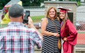 Naugatuck High School graduate Elizabeth Krooss poses for a photo with her mother Victoria Thomas as her father, Richard Krooss, takes a photo following graduation ceremonies Friday at Naugatuck High School. The school held five separate ceremonies with about 40 graduates at each due to limitations on gatherings. Jim Shannon Republican-American