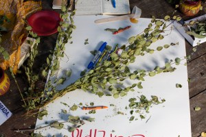 """A branch of eucalyptus on a wooden table where there is a big poster with the word """"eucalipto"""" written upside down on the bottom in red. On the wooden table there are also crayons and markers, a red plastic plate, a yellow handkerchief, two clay jars, some leaves of sage, a small clear plastic container with honey and a wooden stick, and a couple of notebooks, one open and one closed with pens on them. In the bottom left corner there is part of a flyer with information about La morada restaurant. Photo by Cinthya Santos-Briones for Brewing Memories workshop, October 3, 2020."""