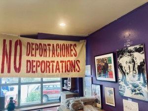 """The walls of La Morada restaurant are filled with photos depicting actions and paintings by Marco Saavedra, an immigration rights activist who helps run La Morada with his family. This photo centers a few of these images and a big banner that says """"NO Deportaciones / NO Deportations"""". Photo credit Angeles Donoso Macaya"""