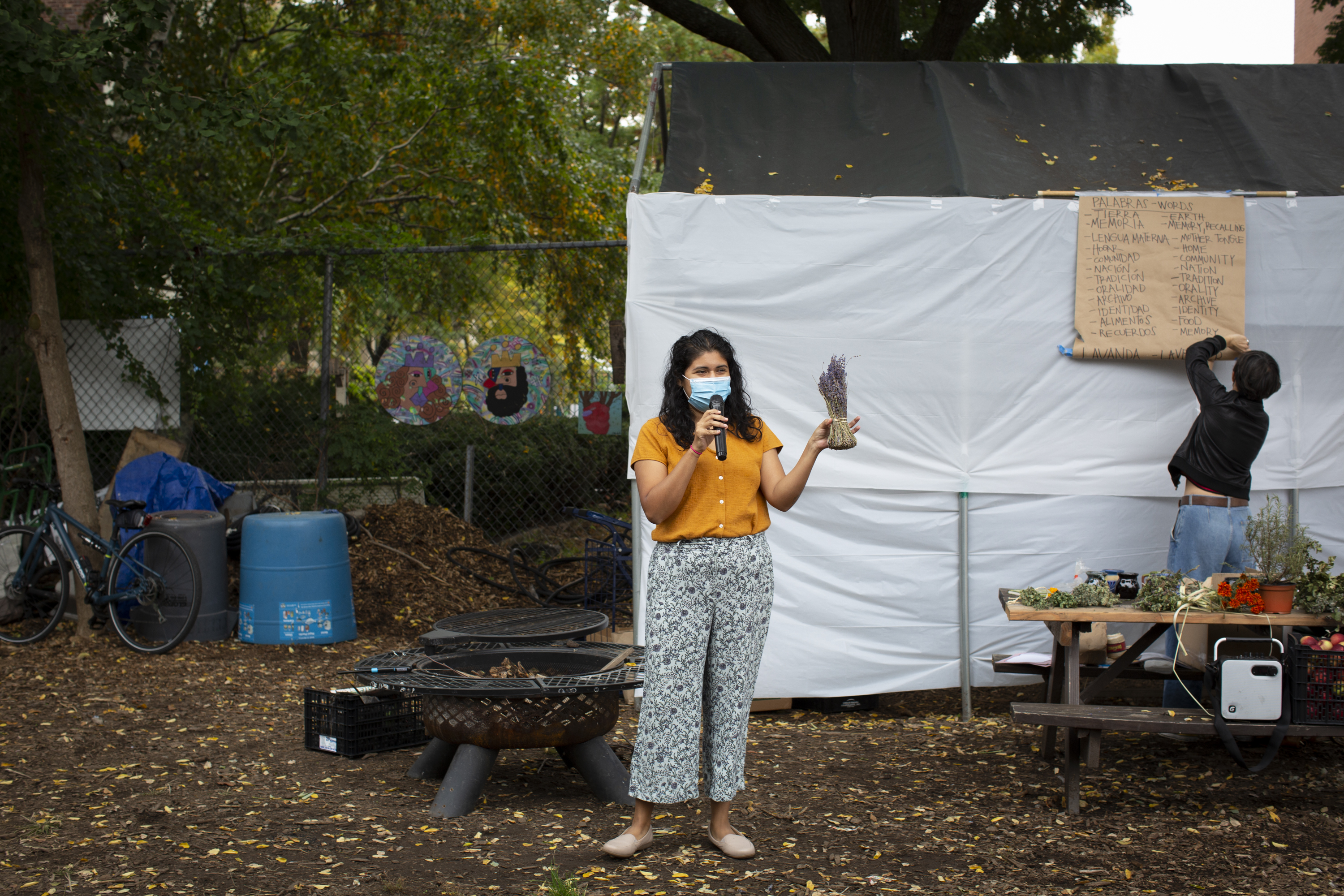 Carolina, wearing an orange shirt, patterned pants, and a medical mask, teaches the properties of lavender. She holds the branch of lavender on her left hand. She wears a medical mask. She stands between the fire pit and the table showcasing the different plants participants will learn about during the workshop. On the bench there is a crate with apples and a speaker. In the back, Angeles, wearing a black jacket and jeans, tries to fix the paper kraft board that shows a list of words in English and Spanish that Carolina will use as part of the activity. Photo by Cinthya Santos-Briones for Brewing Memories workshop, October 24, 2020.