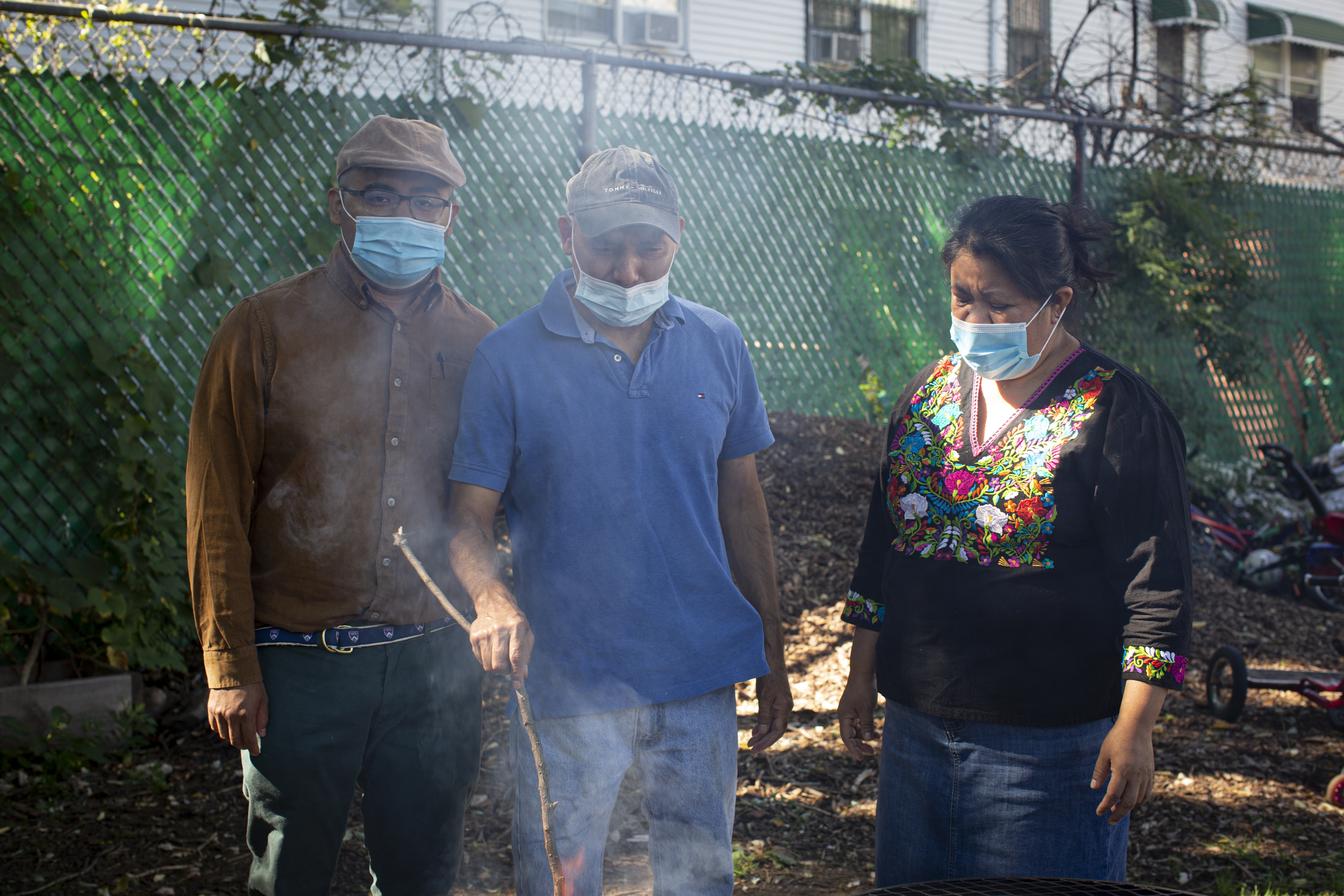 Marco, wearing a light brown shirt, jeans, and a hat, Antonio, wearing a light blue shirt, jeans, and a baseball cap, and Natalia, wearing an Indigenous Mexican embroidered shirt (black with flowers) and a long denim skirt, stand near the fire (out of frame). All three are wearing medical masks. Smoke comes out of the fire. The mounds of soil in the background reflect the morning sunlight. Photo by Cinthya Santos-Briones for Brewing Memories workshop, October 3, 2020.