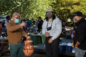 Marco, who is wearing a light brown shirt, green pants, and hat and medical mask, stands near a fire, serving tea to workshop participants of different ages, who stand in line, waiting to be served; the two people in line are also wearing masks––one of whom wears black glasses sunglasses over his gray mask. There's a big pot made out of clay on top of the fire; smoke comes out of the fire. In the background there are other workshops participants. Photo by Cinthya Santos-Briones for Brewing Memories workshop, October 3, 2020.