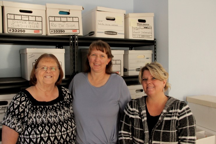 Three women in front of file boxes